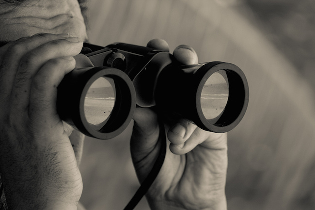 a close-up image of a man looking through binoculars